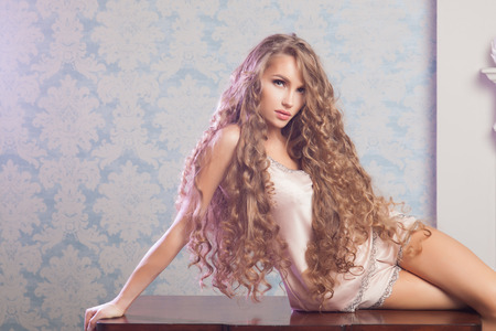 hair and beauty: Sexy blonde woman with fashion make-up and curly hair in vintage bedroom. Skin and hair care concept