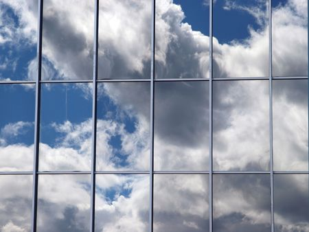 Reflection of clouds in mirror glass windows of a building    Stock Photo