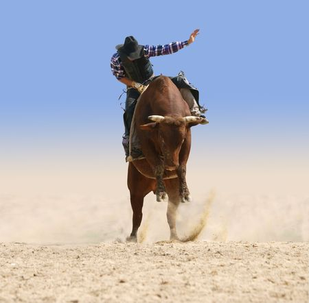 rodeo cowboy: Cowboy Riding a Large Red Bull Stock Photo