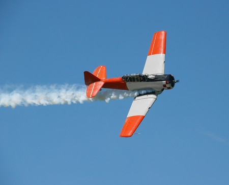 undercarriage: Aerobatic Plane with smoke trail. The cocpit is open Stock Photo