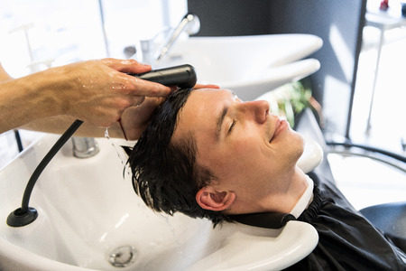 Profile view of a young man getting his hair washed and his head massaged in a hair salon. Imagens