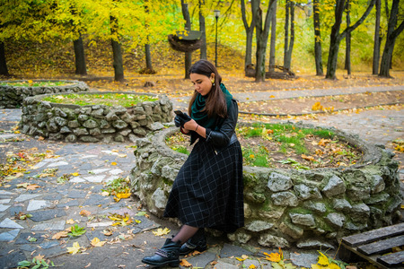 Cute woman is reading pleasant text message on mobile phone while sitting in the park in warm fall day,gorgeous female is searching information on cell telephone