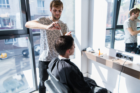 A professional hairstylist with a comb and scissors in his hand styling the wet black and short hair of the man in a hair salon