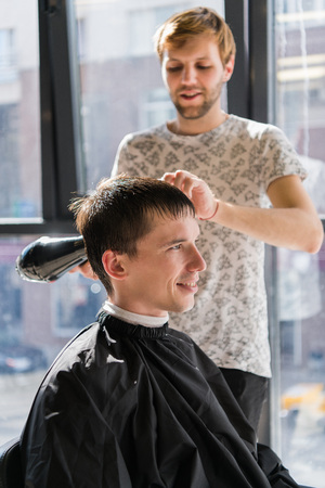 Barber with hairdryer drying and styling hair of client. Styling concept