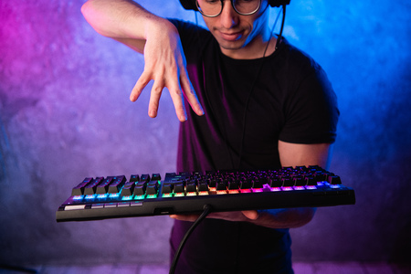 Close-up on gamers hands going to press a key on a keyboard. Background is lit with neon lights