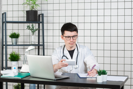 Male doctor in white coat with stethoscope over his neck sitting at table thinking on prescription, writing something down, with box of medicine in his hand
