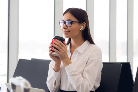 Beautiful girl at international airport, drinking coffee to go while waiting for her flight. Female passenger at terminal, indoors. Traveling people