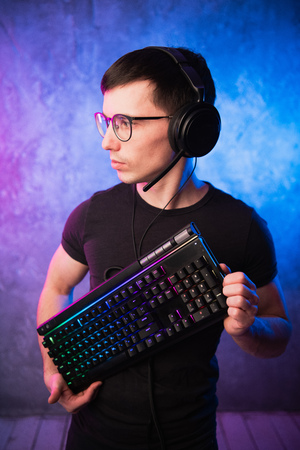 Technology, cyberspace, programming and people concept - hacker man in headset and eyeglasses with keyboard over neon wall