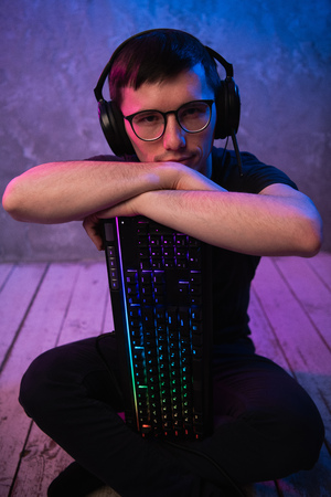 Portrait of the young handsome pro gamer sitting on the floor with keyboard in neon colored room Standard-Bild - 123217058