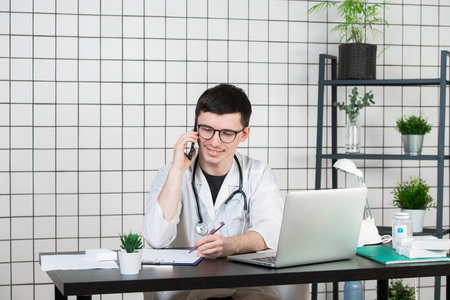 Male doctor using telephone while working on computer at table in clinic