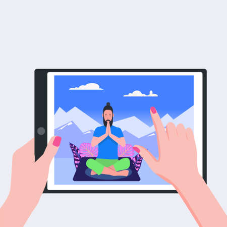 Human hands holding tablet pc with photo of man in yoga lotus practices meditation on silhouette mountains background.