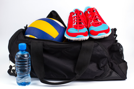 Sports bag with womens sportswear and volleyball ball.