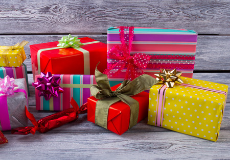 pre: Beautiful gifts on wooden background. Multi-colored boxes with bows. Christmas presents. Pre-Christmas mood. Stock Photo