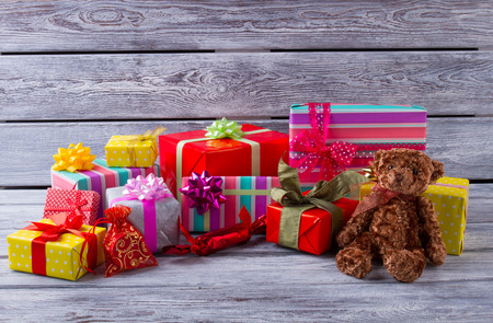 New Year gifts. Many colorful gifts and teddy bear on a wooden background. Gifts for children.