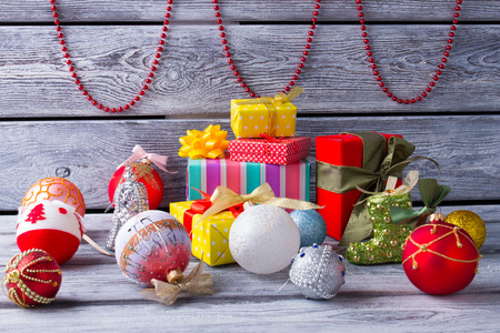 Christmas and New Year decoration. Christmas balls, gift and beads on a wooden background. Stock Photo
