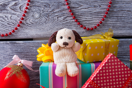 Cute dog is sitting on gifts. Childrens soft toy and pile of gifts. New Year gifts. Stock Photo