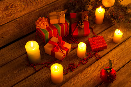 New Year gifts near a Christmas tree. Candles and decorations near a Christmas tree. Stock Photo