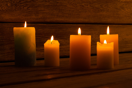 Beautiful yellow candle on dark vintage wooden background. Cozy atmosphere. Decoration for interior. Stock Photo