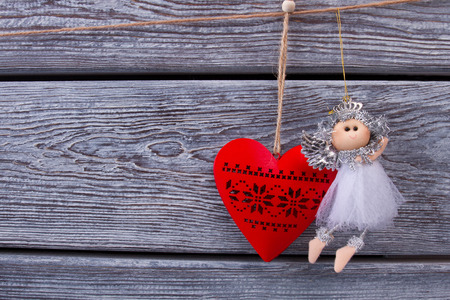 Beautiful little fairy and red wooden heart. Traditional New Years toys. Christmas holidays. Stock Photo
