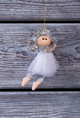night dress: Cute silver fairy hanging on a wooden background. Christmas decoration on the Christmas tree.