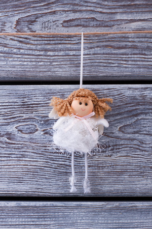 Cute princess on a wooden fence. Christmas toy. Little girl fairy. Stock Photo