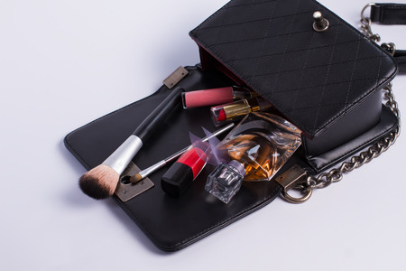 Opened bag with scattered cosmetics. Stock Photo