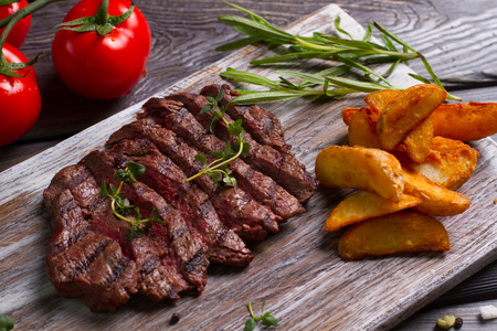 Delicious beef steak with tomato. Meat and rosemary on wooden background.