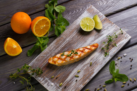 Grilled salmon steak with fresh herbs, fruits and spices on  wooden board.