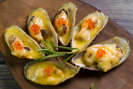 Baked mussels with cheese and eggs on a wooden background. Stock Photo