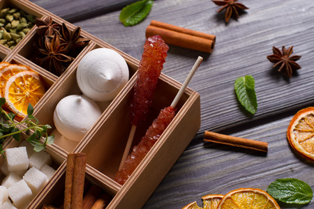 Wooden box with mixed spicy spices, herbs and dried fruit close-up.Sweets for tea.