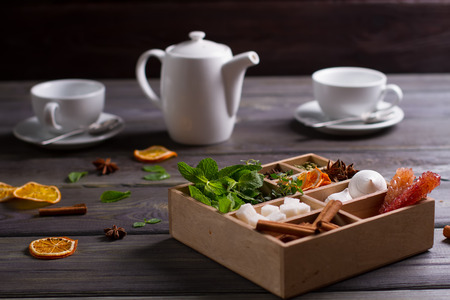 Wooden box with mixed spices, herbs, sweets on the background of tea set.