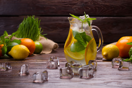 Cold citrusy lemonade in jar with ice and mint.