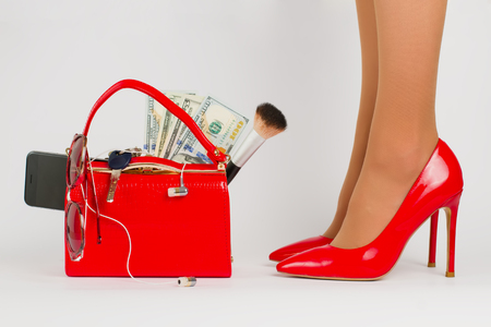 Beautiful female legs in stylish red shoes. Handbag with womens accessories.
