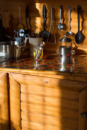 kettles: Wooden kitchen with cooking facilities. Morning sun illuminates the cutlery. Kitchen equipment