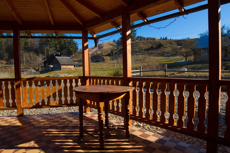 frosty morning: Wooden table stands on the terrace. Beautiful shadows on the terrace in the mountains. Fantastic landscape in the mountains.Cozy courtyard.
