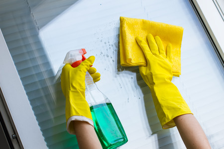 Cleaning windows with special rag and detergent in yellow gloves Stock Photo