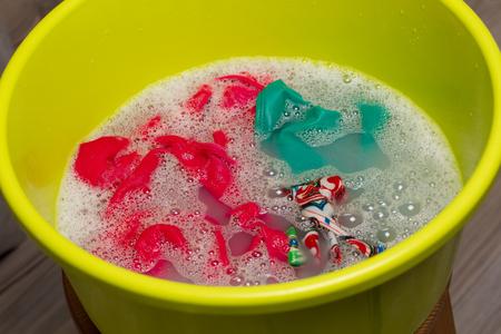 lavamanos: Lavado a mano. Ropa colorida empapada en un tazón.