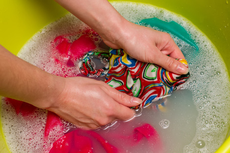 Female hand wash clothes by hand in a bowl.