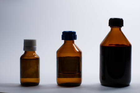 Three silhouettes of different glass bottles with medicine