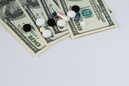 doctor with dollars: Tablets are scattered on the hundred dollar bills.