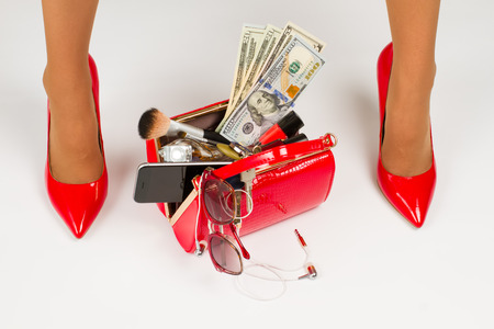 Beautiful legs in red shoes. Red bag with accessories. Stock Photo