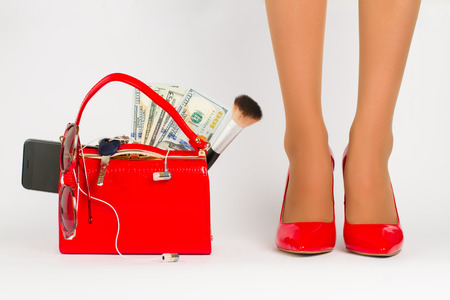 Beautiful female legs in shoes stand near handbag with accessories.