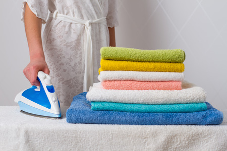 housewife  standing at the ironing board ironing towels