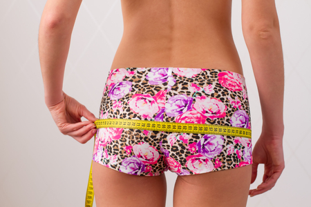 girl in colored panties measures hips Stock Photo