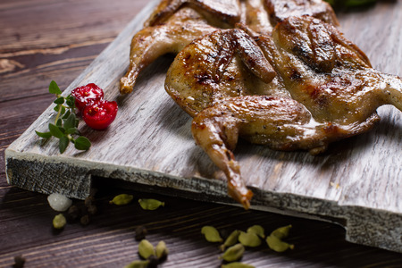 Two roasted quails with spices on a wooden background.