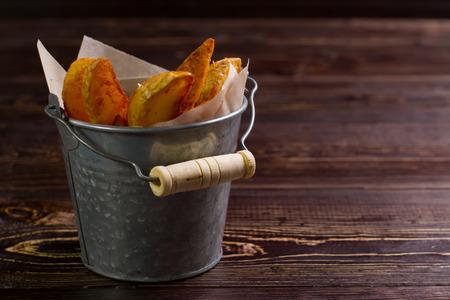 Roast potatoes in a bucket on a wooden. Stock Photo