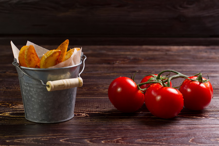 Fried potatoes with tomatoes on wooden. Stock Photo