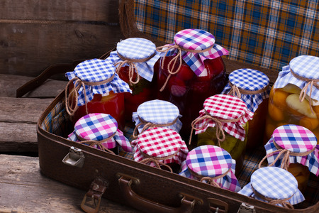 Glass jars with preservation in an old suitcase. Wooden shelves of old boards.