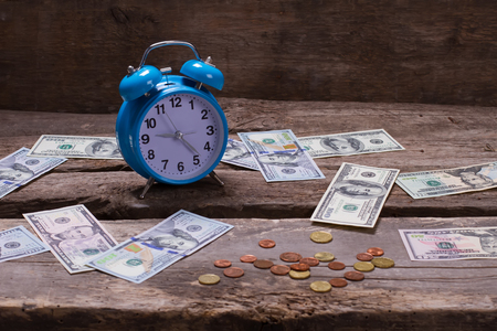 Dollars and cents on the vintage background. Beautiful retro alarm clock on a wooden shelf.