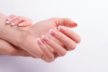 Beautiful well-groomed female hands. Classic French manicure on a white background. Stock fotó